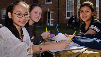girls doing school work outdoors